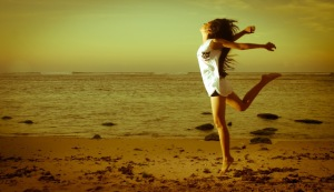 girl-jumping-sand-beach
