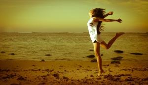 girl-jumping-sand-beach